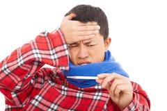 Sjuk ung man som mäter febertemperatur med termometern Fotografering för Bildbyråer