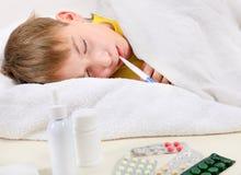 Sjuk unge i sängen Arkivfoto