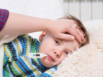 Sjuk unge med hög feber som lägger i säng och modern som tar tempera Royaltyfria Bilder