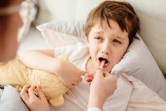 Sjuka åtta år pojke i sänglidande från halsen smärtar royaltyfria foton