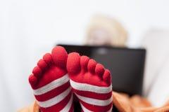Sjuka kvinnor i roliga toesocks på soffan Arkivbilder