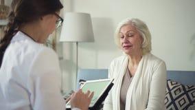 Sjuka mogna kvinnor för ungt sjuksköterskabesök på hennes hus stock video