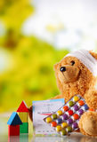 Sjuka Teddy Bear med preventivpillerar, kortet och Shape kvarter Royaltyfria Bilder