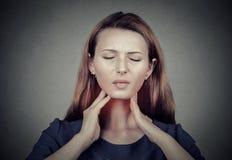 Sjuka unga kvinnan som den har, smärtar i hennes hals arkivbild