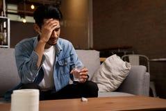 Sjukdom och sjukligt villkorbegrepp Huvudvärkman som sitter på soffan arkivbilder
