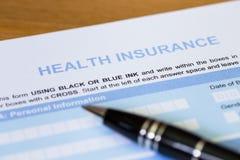 Sjukförsäkringansökningsblankett med pennan Arkivbild