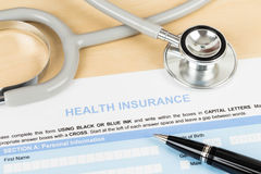 Sjukförsäkringansökningsblankett med pennan och stetoskopet Arkivbild