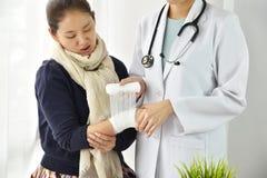 Sjukförsäkringolycksreklamationen, doktorsinpackning sårar handledarmen med murbruk förbinder, den tålmodiga handen för kvinnan s arkivfoton