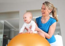 Sjukgymnastik med behandla som ett barn på en konditionboll Arkivbilder