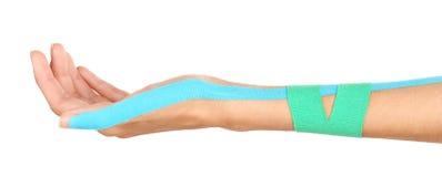 Sjukgymnastikbegrepp Kvinnlig hand med physio vitbakgrund för band n royaltyfria foton
