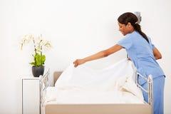 Sjukhus: Kvinnlig sjuksköterska Making sängen Arkivbilder