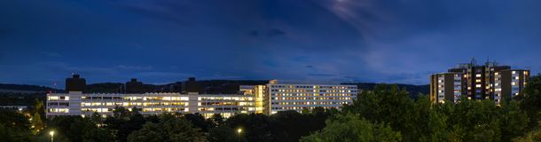 Sjukhus vid natt med tända fönster som utgör hjärta Arkivfoton