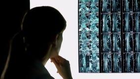 Sjukhusallmäntjänstgörande läkare som kontrollerar patientröntgenstrålen, diagnostik för ryggrads- skada och behandling royaltyfria foton