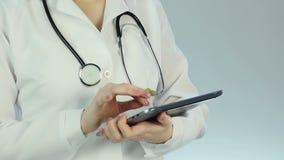 Sjukhusdoktor som kontrollerar patients medicinska historia i elektroniskt kliniskt rekord arkivfilmer
