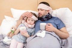 Sjuklig förkylda flicka och pappa Arkivfoton