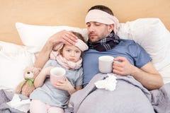 Sjuklig flicka och pappa som har te Arkivbild