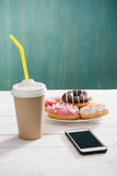 Sjuklig frukost med kaffe som går, plattan av frostade donuts och smartphonen med den svarta skärmen på trätabellen Arkivbilder