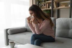 Sjuklig kvinna som sitter på soffainnehavsilkespappret som torkar hennes näsa royaltyfria bilder