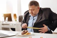 Sjuklig sjukligt fet anställd som ser angången Arkivfoton
