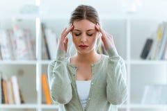 Sjuklig ung kvinna med huvudvärken som hemma trycker på hans huvud royaltyfri bild