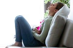 Sjuklig ung kvinna med magknip genom att använda en varmvattenpåse, medan sitta på soffan hemma arkivfoto