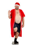 Sjukligt fet jultomten som har gyckel på våg Arkivbild