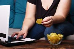 Sjukligt fet kvinna med bärbara datorn, skräpmat och öl arkivbilder
