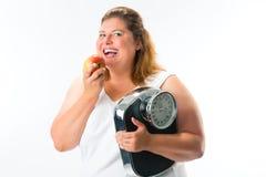 Sjukligt fet kvinna med skalan under armen och äpplet Royaltyfria Bilder
