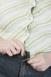 Sjukligt fet kvinna som försöker att knäppas jeans Royaltyfria Bilder