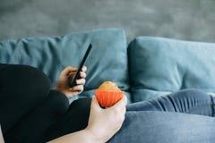 Sjukligt fet kvinna som lägger på soffan som äter muffin Royaltyfri Fotografi
