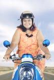 Sjukligt fet kvinna som rider en motorcykel på huvudvägen Fotografering för Bildbyråer