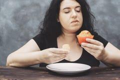 Sjukligt fet kvinna som väljer den between lilla och stora muffin Arkivfoton