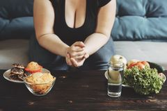 Sjukligt fet kvinna som väljer mellan sunt och skräpmat Arkivfoto