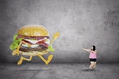 Sjukligt fet kvinnaspring i väg från en hamburgare royaltyfria bilder