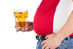 Sjukligt fet man med den stora buken som rymmer ett exponeringsglas av uppfriskande kallt öl Royaltyfria Foton
