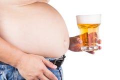 Sjukligt fet man med den stora buken som rymmer ett exponeringsglas av uppfriskande kallt öl Royaltyfri Fotografi