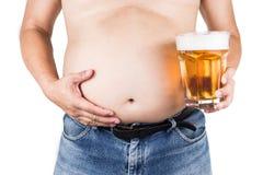 Sjukligt fet man med den stora buken som rymmer ett exponeringsglas av uppfriskande kallt öl arkivbilder