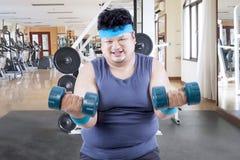 Sjukligt fet man som övar med skivstånger i idrottshallmitt arkivbilder