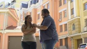 Sjukligt fet man som kramar den blyga flickvännen, förtroendefullt förhållande i par, osäkerheter arkivfilmer