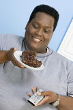 Sjukligt fet man som ser bakelse Fotografering för Bildbyråer