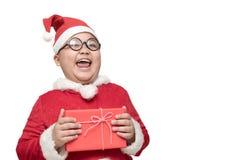 Sjukligt fet fet pojke, i ask och att skratta för gåva för Santa Claus dräkt hållande Arkivbilder
