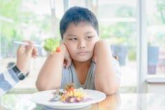 Sjukligt fet pojke med uttryck av avsmak mot grönsaker royaltyfria bilder