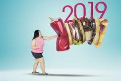 Sjukligt feta kvinnastansmaskiner snabbmat och nummer 2019 royaltyfri foto