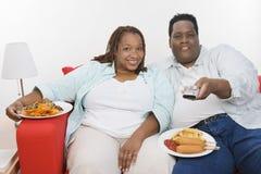 Sjukligt feta par som tillsammans sitter Arkivbild