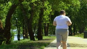 Sjukligt fett manligt jogga parkerar in och att försöka att förlora vikt, sporten och sund livsstil stock video