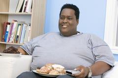 Sjukligt fett mansammanträde på soffan Arkivfoton