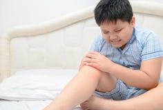Sjukligt fett pojkelidande från knä smärtar och sitter på säng, arkivbilder