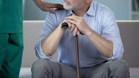 Sjukskötare som stöttar den åldriga mannen, pensionärsammanträde på soffan på vårdhemmet lager videofilmer