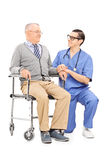 Sjukskötare som talar till en hög patient Arkivfoto