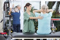 Sjuksköterska Assisting Senior Woman i tillbaka övning i Rehabmitt royaltyfri bild